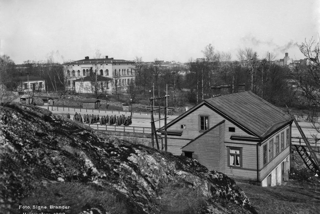 Hakasalmen huvila Turuntien varrella. Tiellä marssii sotilaiden joukko.
