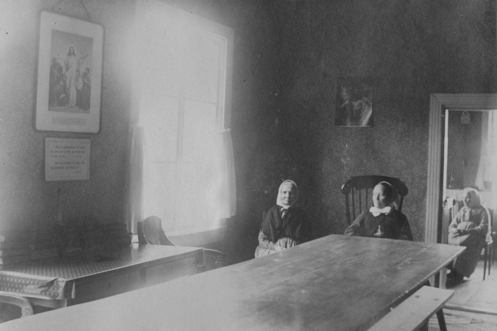 Kolme naista istuu hämärässä huoneessa.