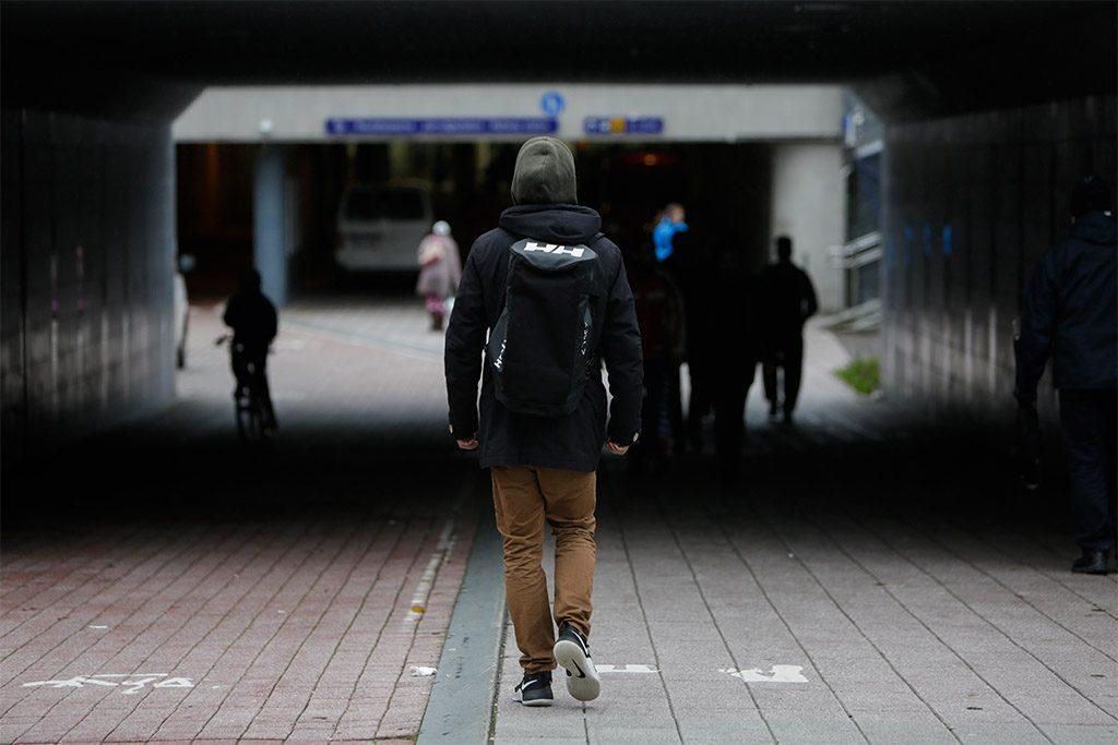 Nuori mies kävelee alikulkutunnelissa, selkä on kameraan päin.