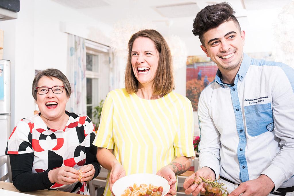 Kolme hymyilevää henkilöä keittiön pöydän ääressä.