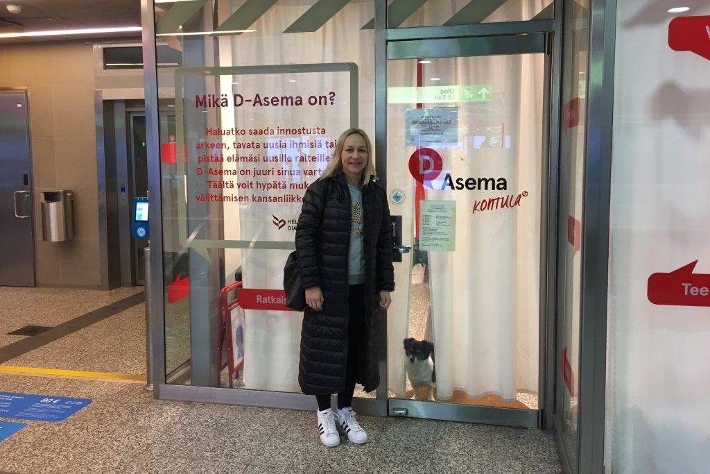 Saija Karjala seisoo D-asema Kontulan ulko-ovella. Ovessa on teksti D-asema Kontula ja Mikä on D-asema?.