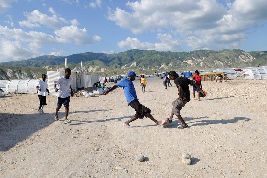 Pojkar spelar fotboll på en sandstrand.
