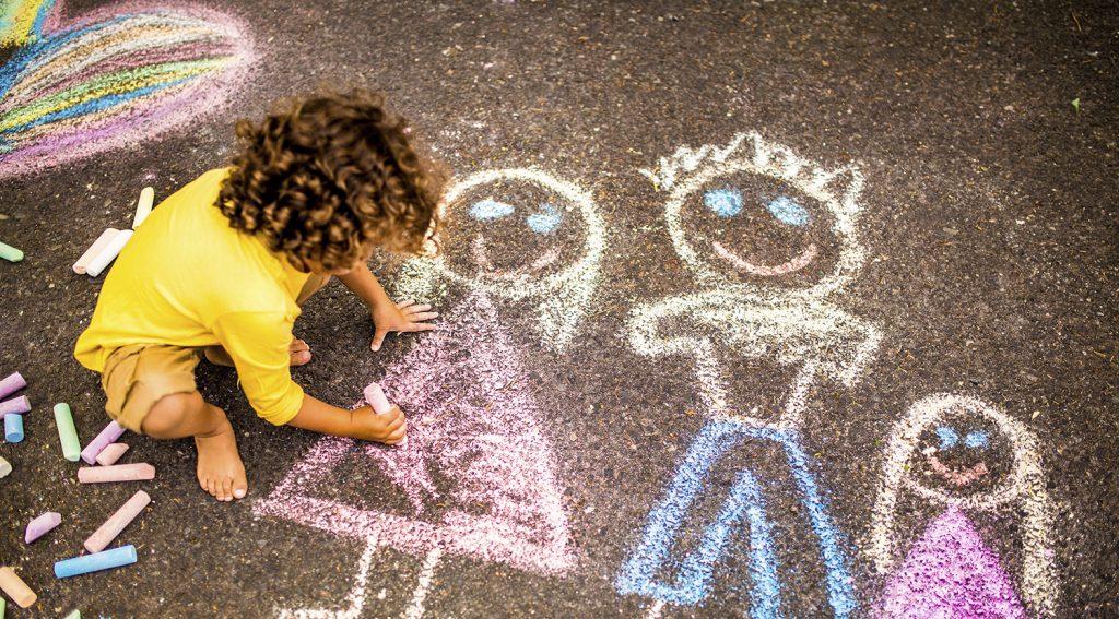 Lapsi piirtää katuun liiduilla.