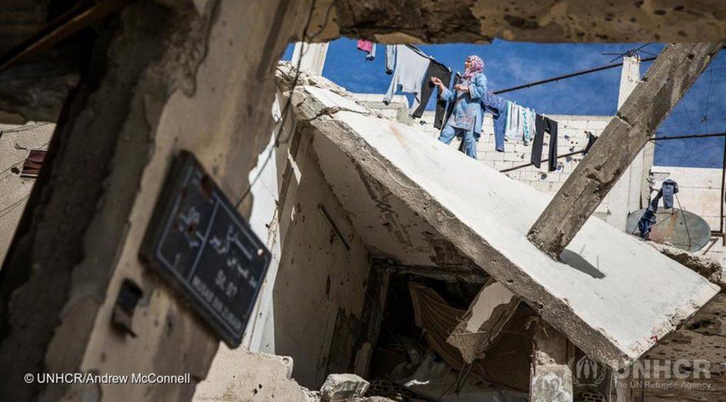 Pommituksessa tuhoutunut talo. Nainen on talon katolla ripustamassa pyykkiä narulle kuivumaan.