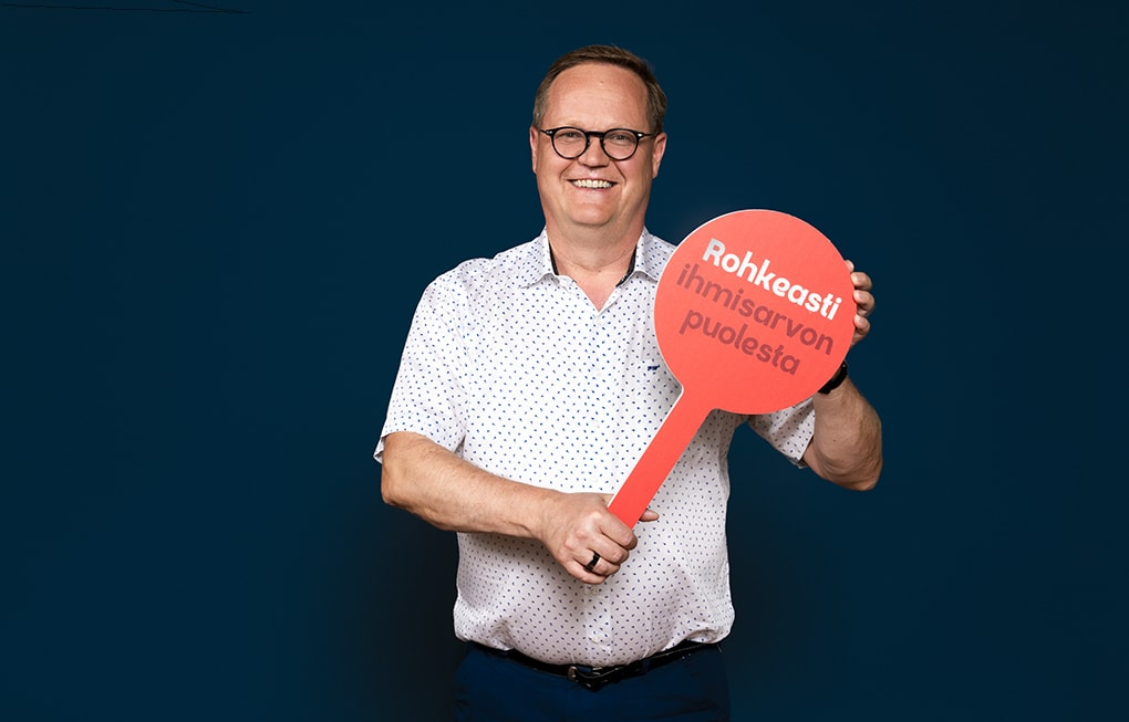 Toimitusjohtaja Olli Holmström. Hänellä on kädessään kyltti Rohkeasti ihmisarvon puolesta.