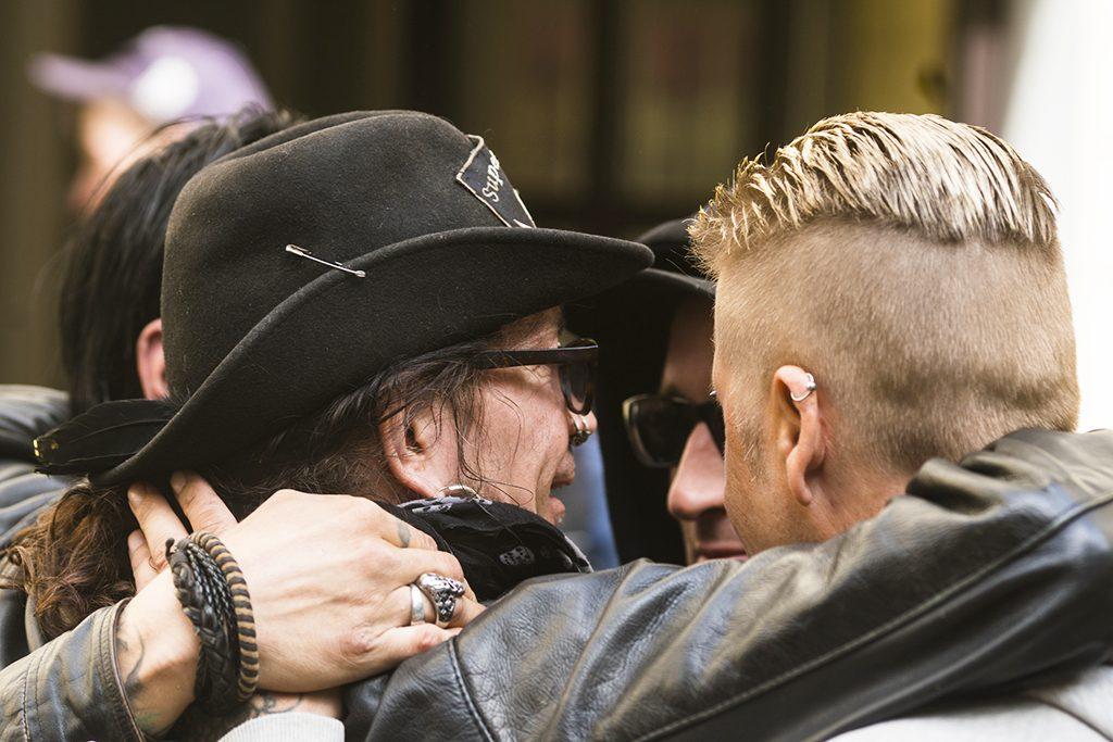Neljä miestä halaa toisiaan. Ihmisarvo on myös tunne omasta tärkeydestä toisille..