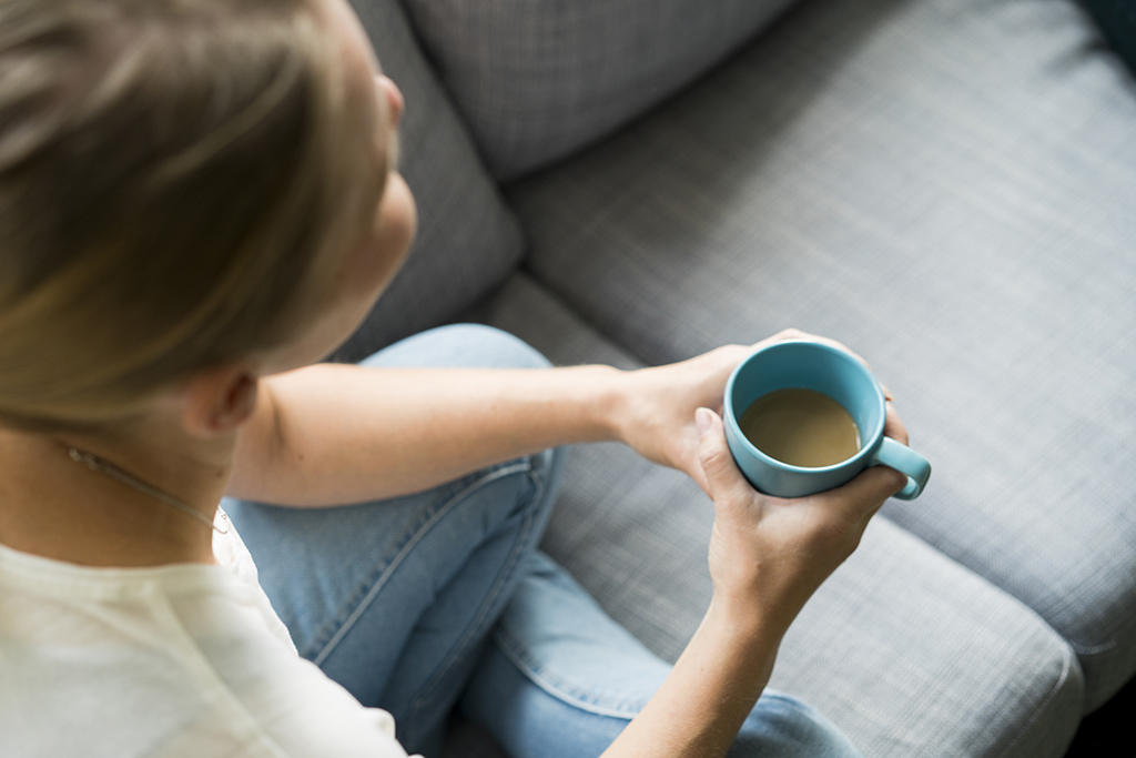 Nainen istuu sohvalla. Hänellä on kahvikuppi kädessä.