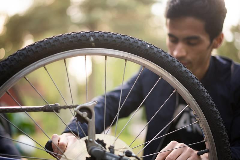 Nuori mies korjaa polkypyörää.