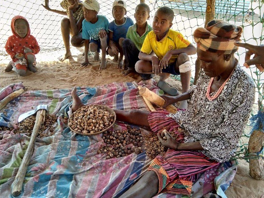Nainen istuu maassa. Hänen edessään on astiassa papuja. Lapset katsovat vieressä. Kansainvälinen työ osa Diakonissalaitoksen toimintaa.