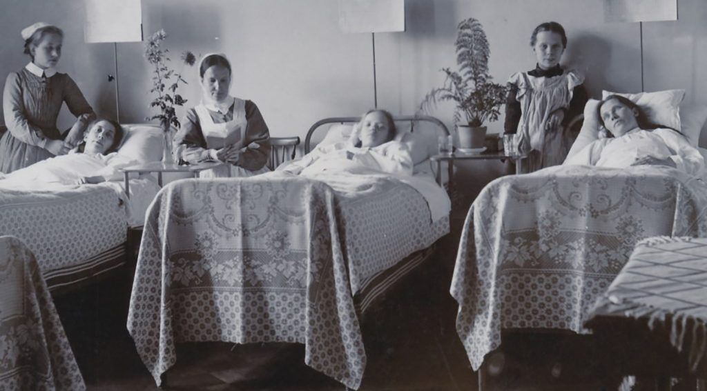 Kolme potilasta vuoteissaan, kahden vierellä on hoitaja ja yhden vierellä ehkä vierailija.