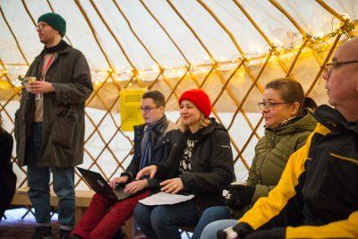 Ihmisiä istumassa jurtassa, joka on kanslaistoiminnan tila Helsingin Kontulassa.