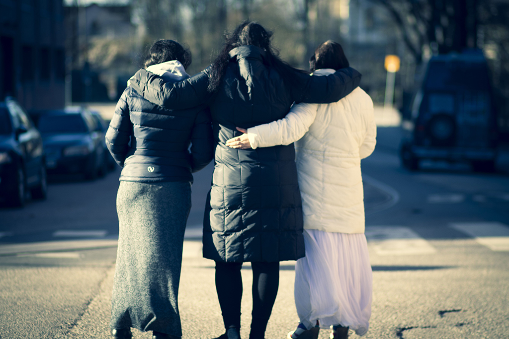 Kolme romanialaista romaninaista kävelemässä käsikynkkää kadulla.