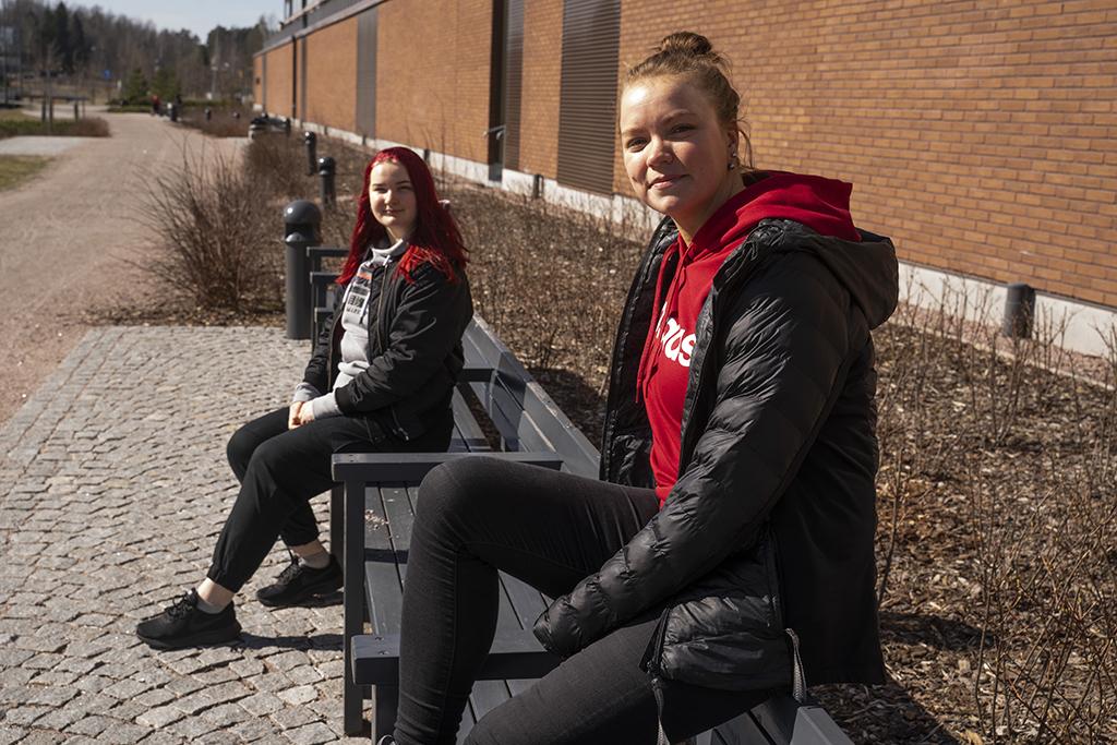 Kaksi nuorta naista, Kätriin ja Emmi istuvat puistonpenkillä.