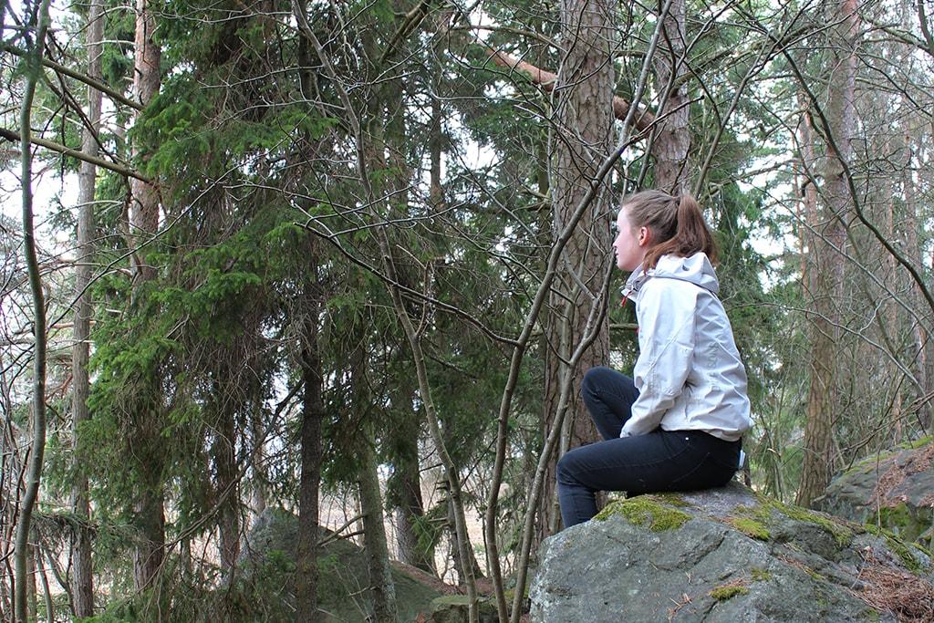 Nuori tyttö istuu suuren kiven päällä.