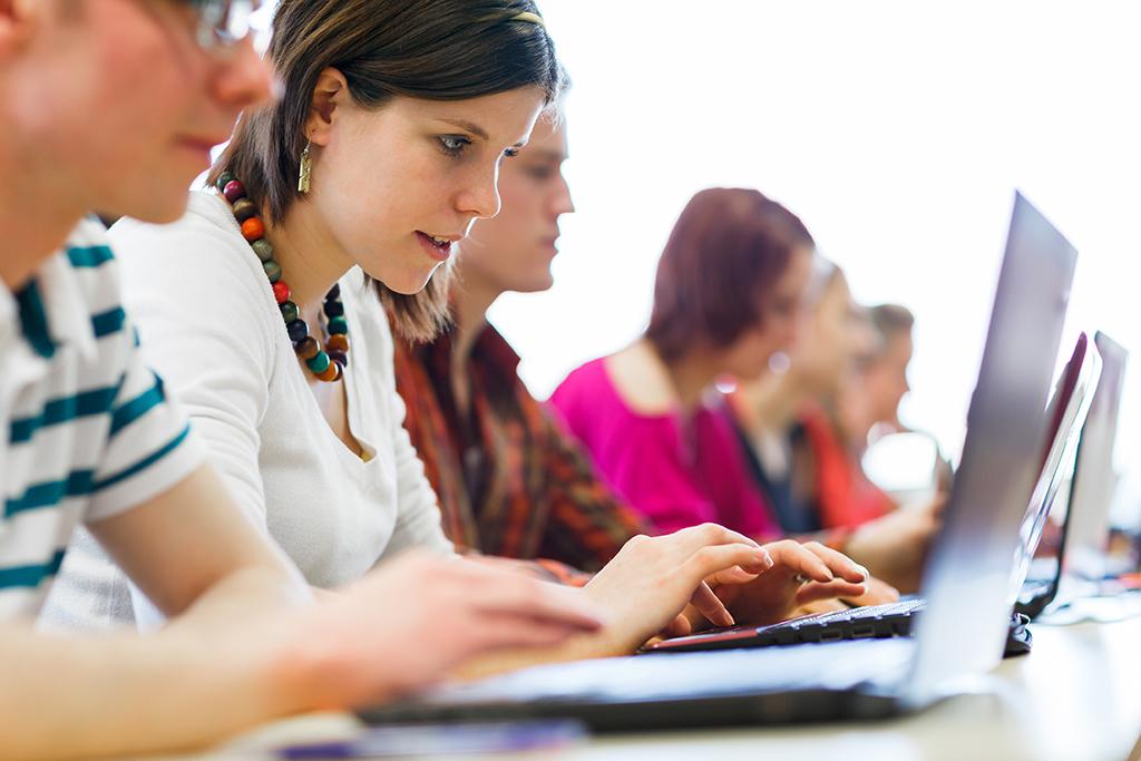 Ryhmä nuoria naisia on tietokoneruutujen edessä.