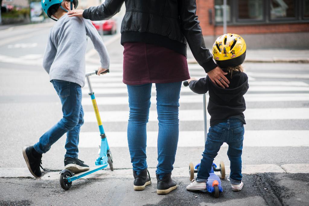 Nainen ja kaksi lasta ylittämässä katua. Perheen mukana -palvelu on vaikuttavuusinvestointi