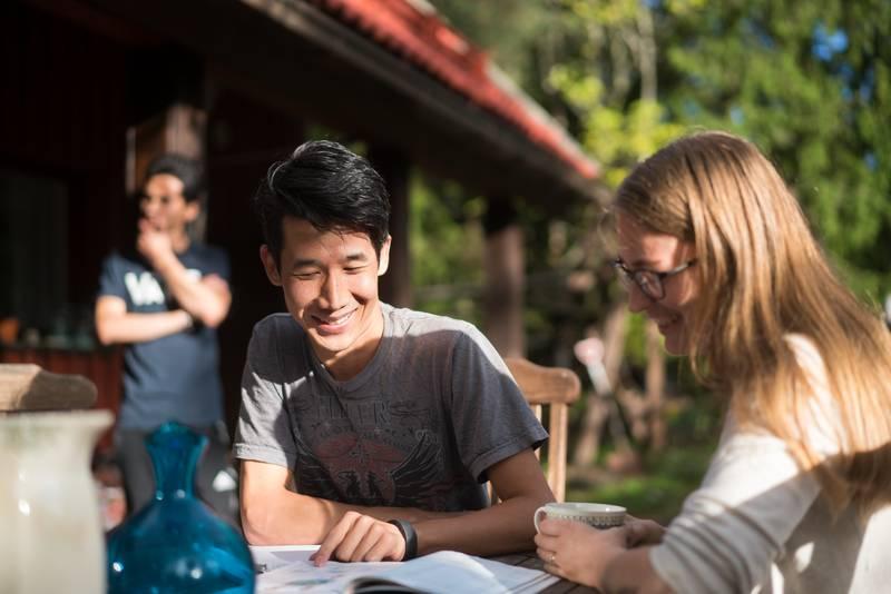 Nainen ja nuori mies pöydän ääressä tutkimassa kirjaa. Taustalla toinen mies.