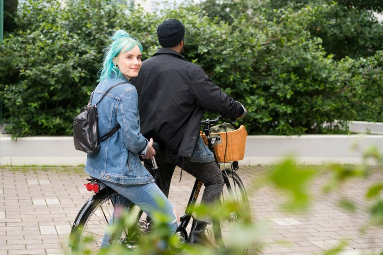 Nuori mies ja nainen ajavat polkupyörällä.