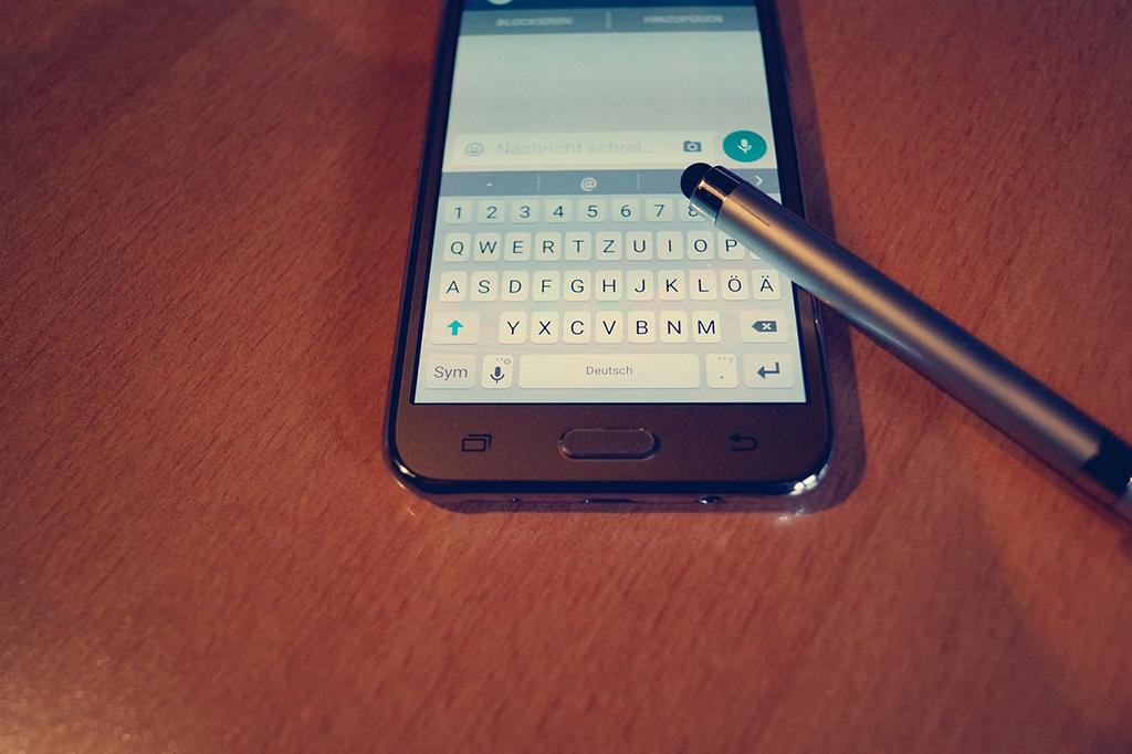 Matkapuhelin pöydällä ja sen päällä kynä.