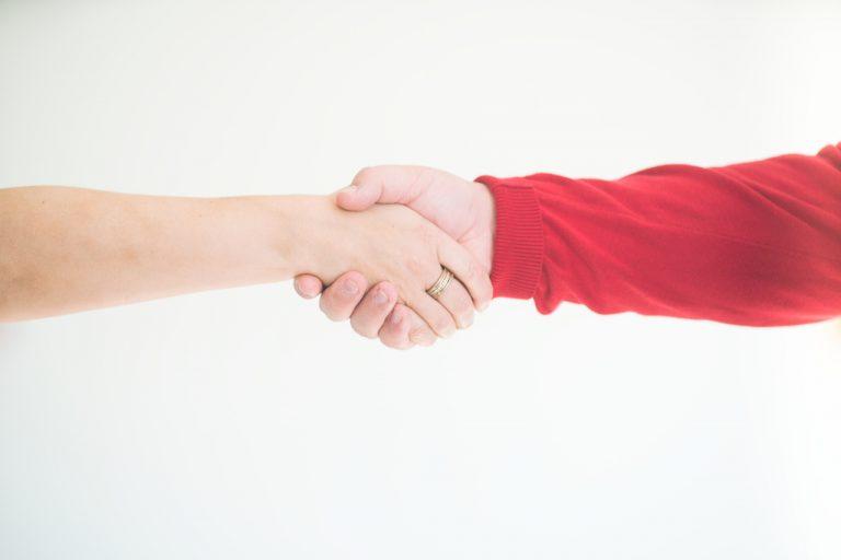 kaksi henkilö kättelee toisiaan.