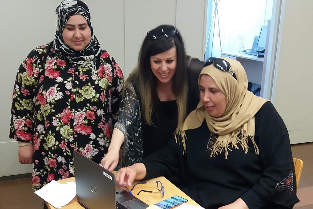 Kolme naista tietokoneen ääressä.