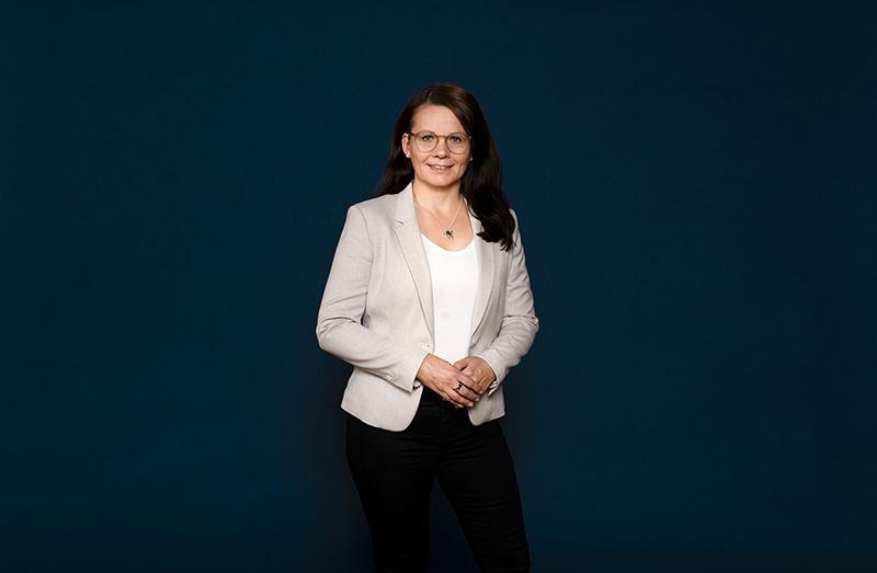 Vaaleaan jakkutakkiin pukeutunut Jaana Laaksonen seisoo tummansinisen seinän edustalla hymyileväisenä.