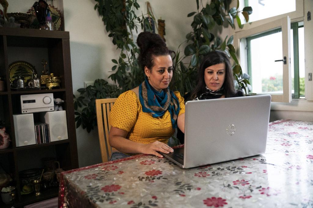 Kaksi naista istuvat pöydän ääressä tietokoneella työskennellen. Maahanmuuttajien työllistyminen on heille yhteinen aihe.
