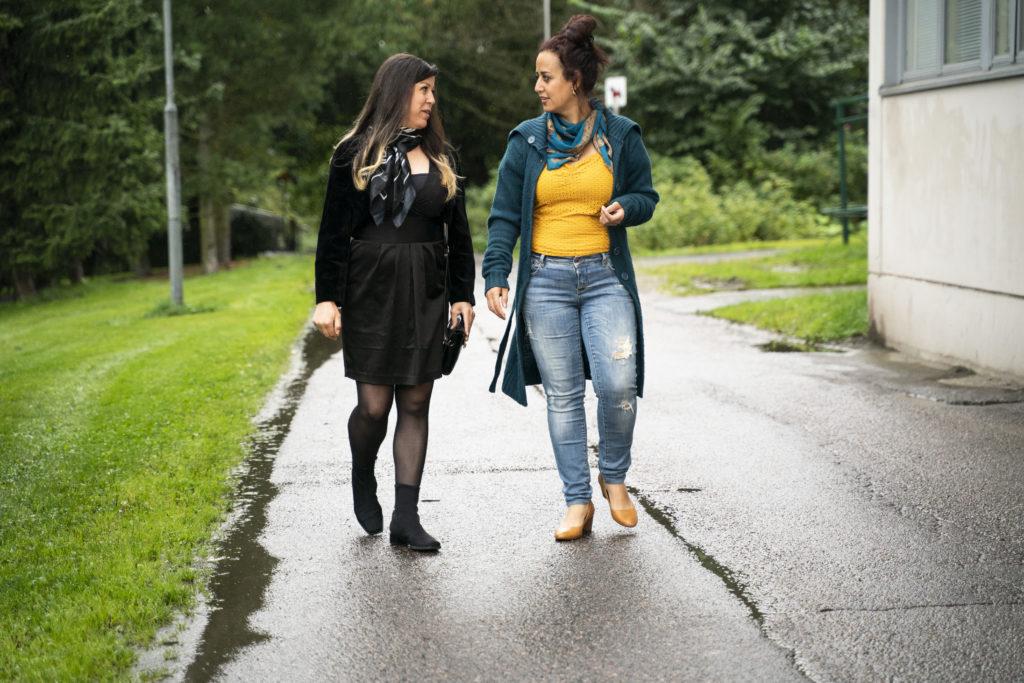 Kaksi naista kävelevät sateesta märällä asfalttitiellä, toistensa kanssa keskustellen.