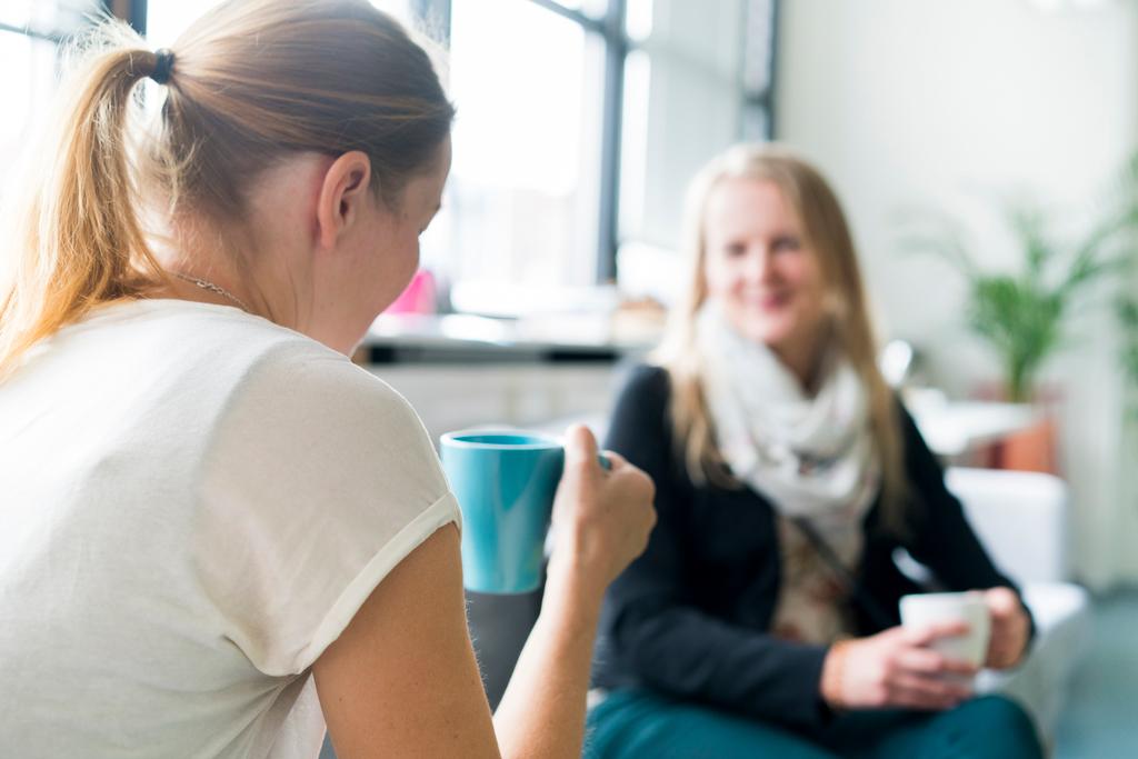 Kaksi naista istuu sohvalla, kummallakin on kahvikupit käsissään.