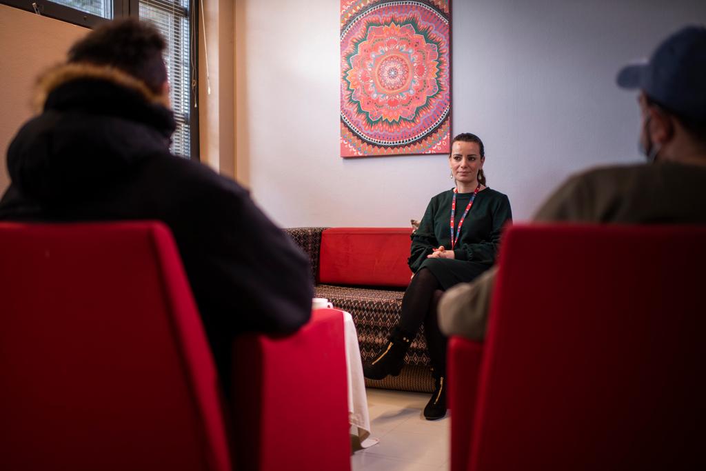 Nainen istuu punaisella sohvalla. Häntä vastapäätä istuu kaksi henkilöä omilla tuoleillaan, mutta näistä kahdesta henkilöstä näkyy ainoastaan takaapäin sivuprofiili.