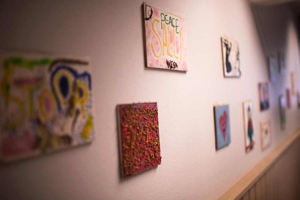 Vaalealla seinällä on erivärisiä pieniä tauluja aseteltuna eri kohdille.