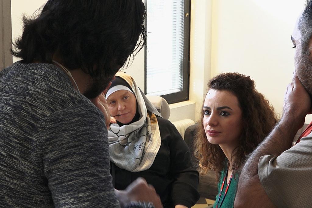 Paperittomien päiväkeskuksen työntekijät Anne Hammad ja Nadia Hellsten keskustelevat kahden miehen kanssa.