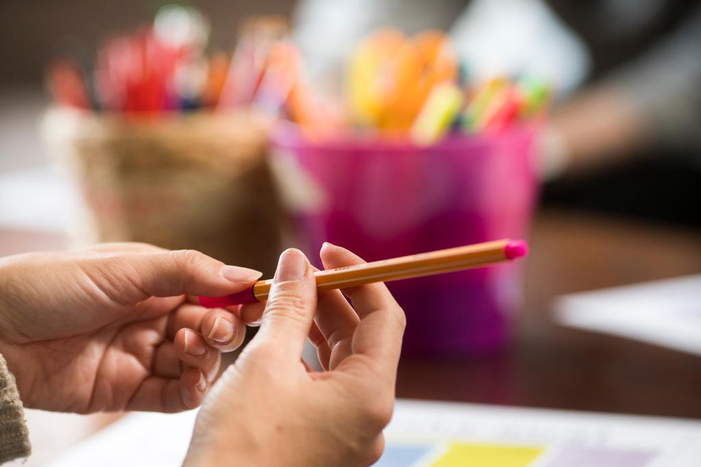 Naisen kädet, hän pitää kynää kädessään. Vamos-Akatemia on keskustelua NEET-nuorten tilanteesta.