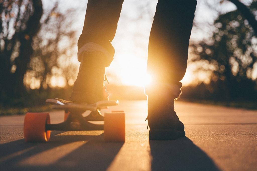 Jalka skeittilaudan päällä, toinen vieressä. Taustalla auringon nousu tai lasku. Vamos Flow työskentelee maahanmuuttajanuorten parissa.