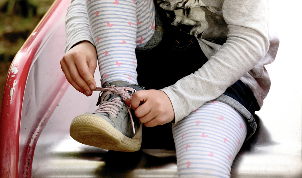 Lapsi sitoo kengännauhoja. 19.2. vietettiin Care Day -tapahtumaa.