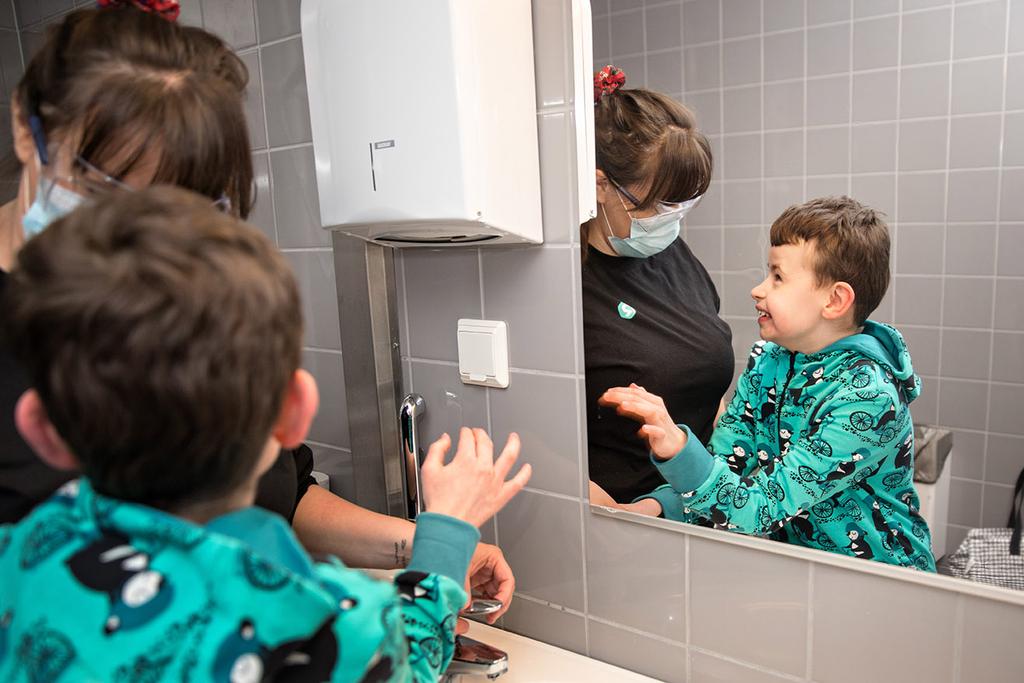 Lapsi ja ohjaaja kylpyhuoneessa peilin edessä.