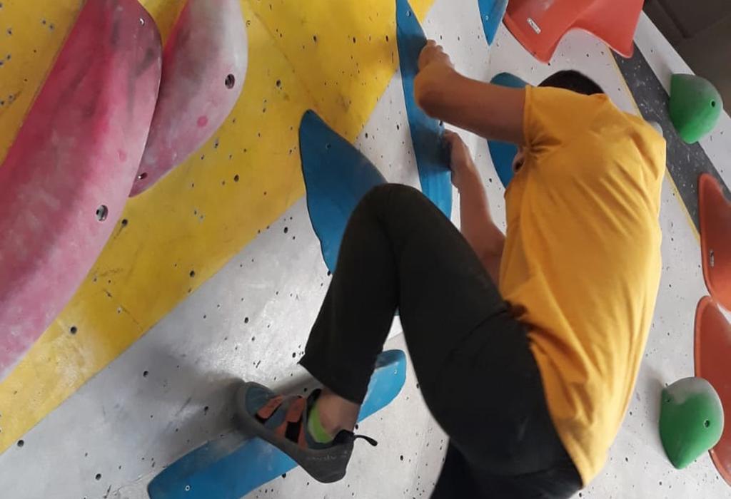 Mies kiipeää kiipeilyseinää ylös. Yrityslahjoitus, sillä autat nuoria eteenpäin elämässä.