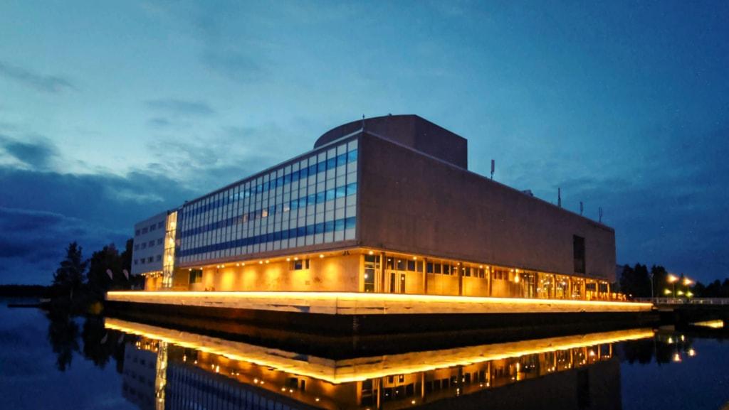 Oulun veden äärellä oleva teatterirakennus. Sen alaosa on valaistu.
