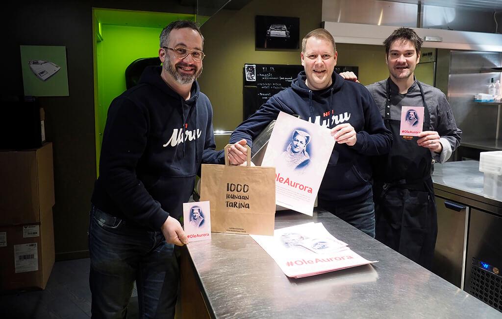 Samuil Angelov, Timo Linnamäki ja Henri Alen ravintolan keittiössä. Ruokalahjoitus Tuhannen annoksen tarina valmistetaan kokkien keittiössä. Heillä on käsissään kassi, jossa lukee 1000 lounaan tarina ja postikortteja, joissa lukee Ole Aurora.