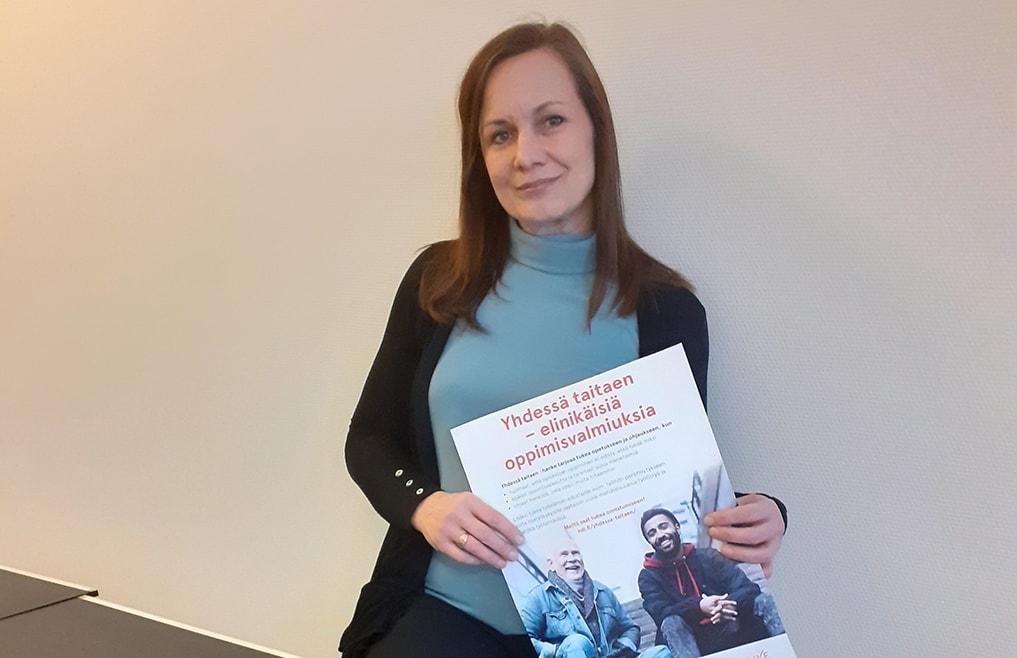 Emma Nylund pitää kädessään julistetta, jossa teksti Yhdessä taitaen - elinikäisiä oppimisvalmiuksia. Se on hankejuliste. Hankkeen tavoitteena on elinikäinen oppiminen.