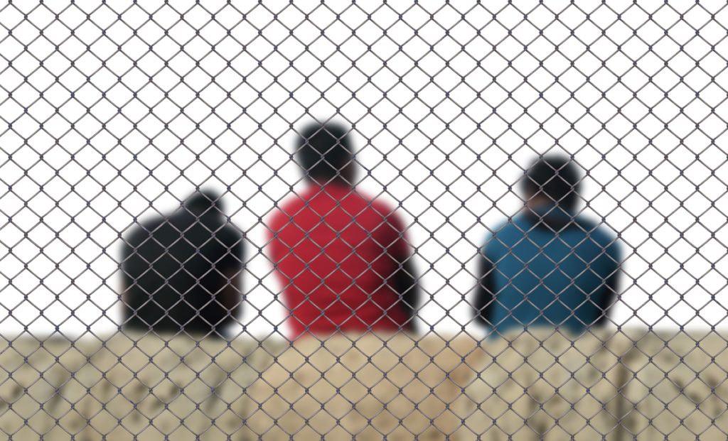 Kolme miestä istuu verkkoaidan takana.