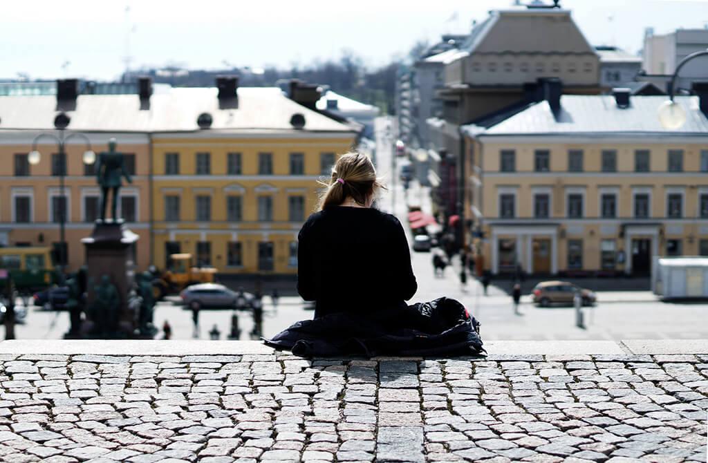 Tyttö, joka istuu Helsingin tuomiokirkon portailla