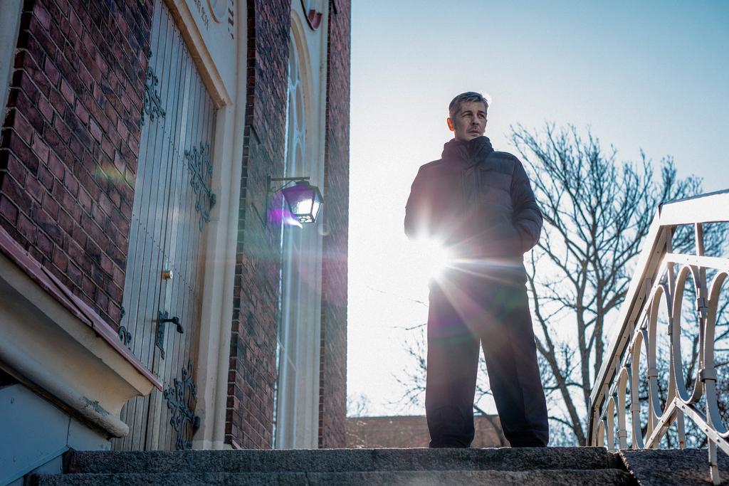 Mies seisoo ulkona rakennuksen edessä. Taustalla kirjas taivas ja auringon kajo.