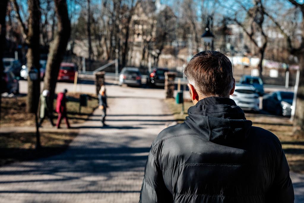 Mies seisoo tien päässä, taustalla näkyy parkkipaikka ja muutama ohikulkeva henkilö.