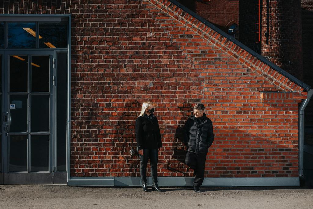 Kaksi henkilöä seisoo punatiilisen seinän edustalla.