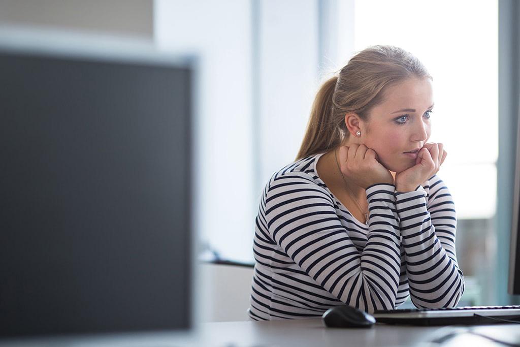Nainen katsoo huolestuneena tietokoneen ruutua. Taloustaito-hanke voisi olla hänelle avuksi.