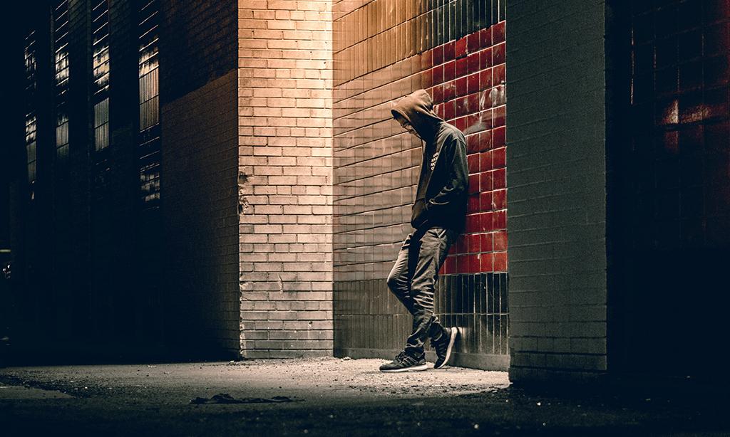 Huppupäinen ihminen nojaa seinään.