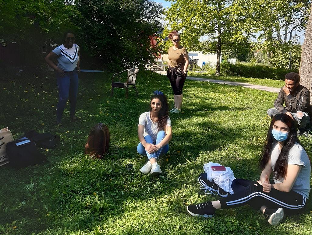 Ryhmä nuoria istumassa nurmikolla.