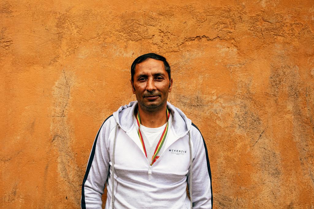 Mies seisoo oranssin tiiliseinän edustalla.