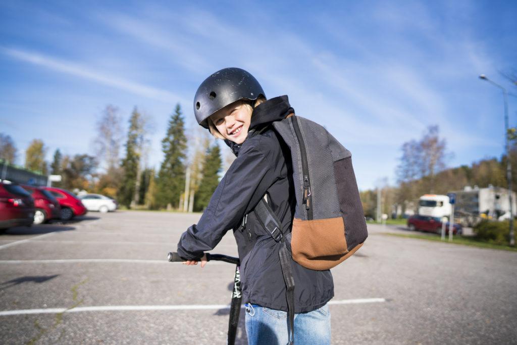 Poika katsoo taakseen pyörän selästä ja hymyilee kamaralle parkkipaikalla.